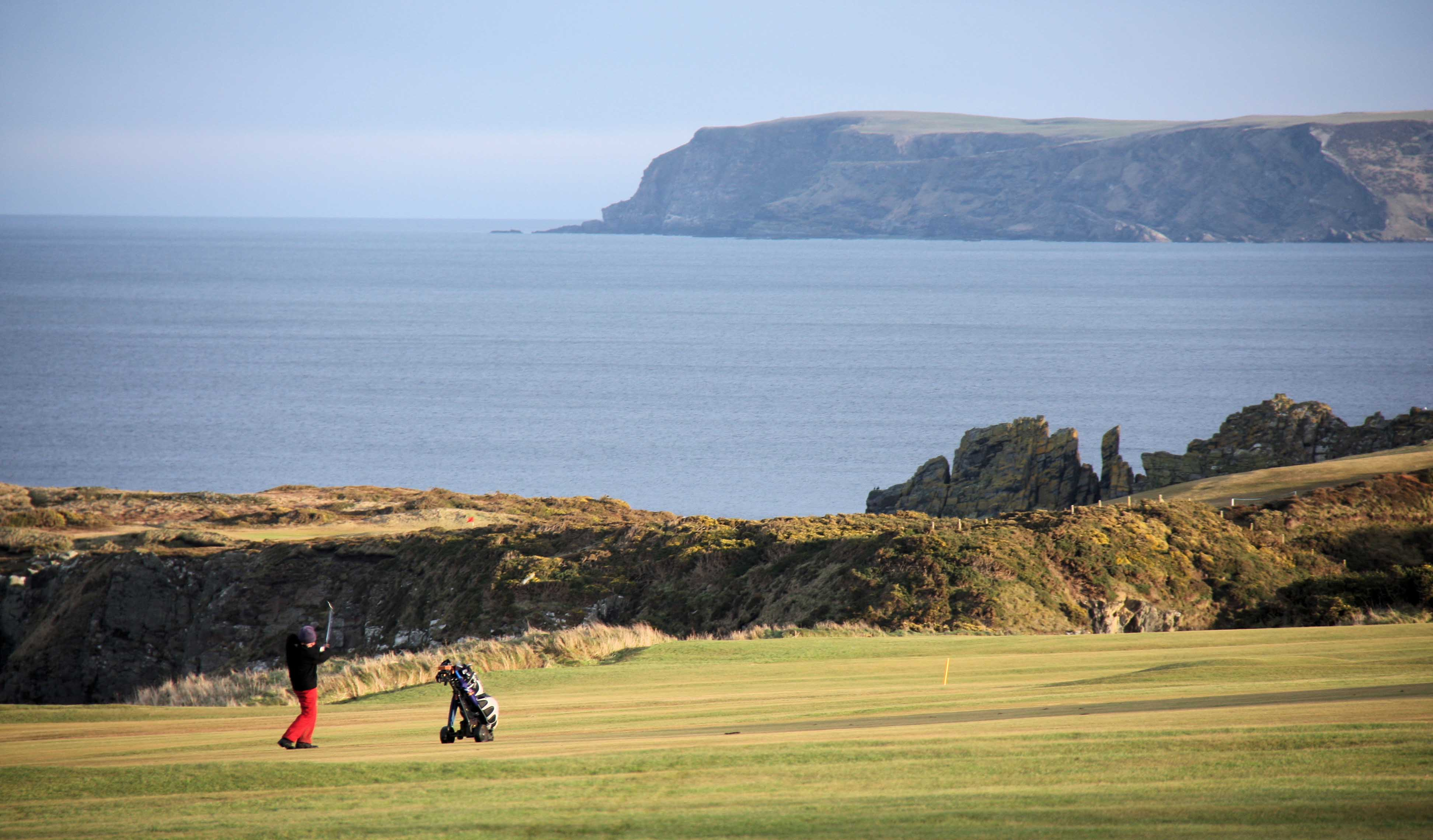 A golfer by the coastline and cliffs, Aberdeen.