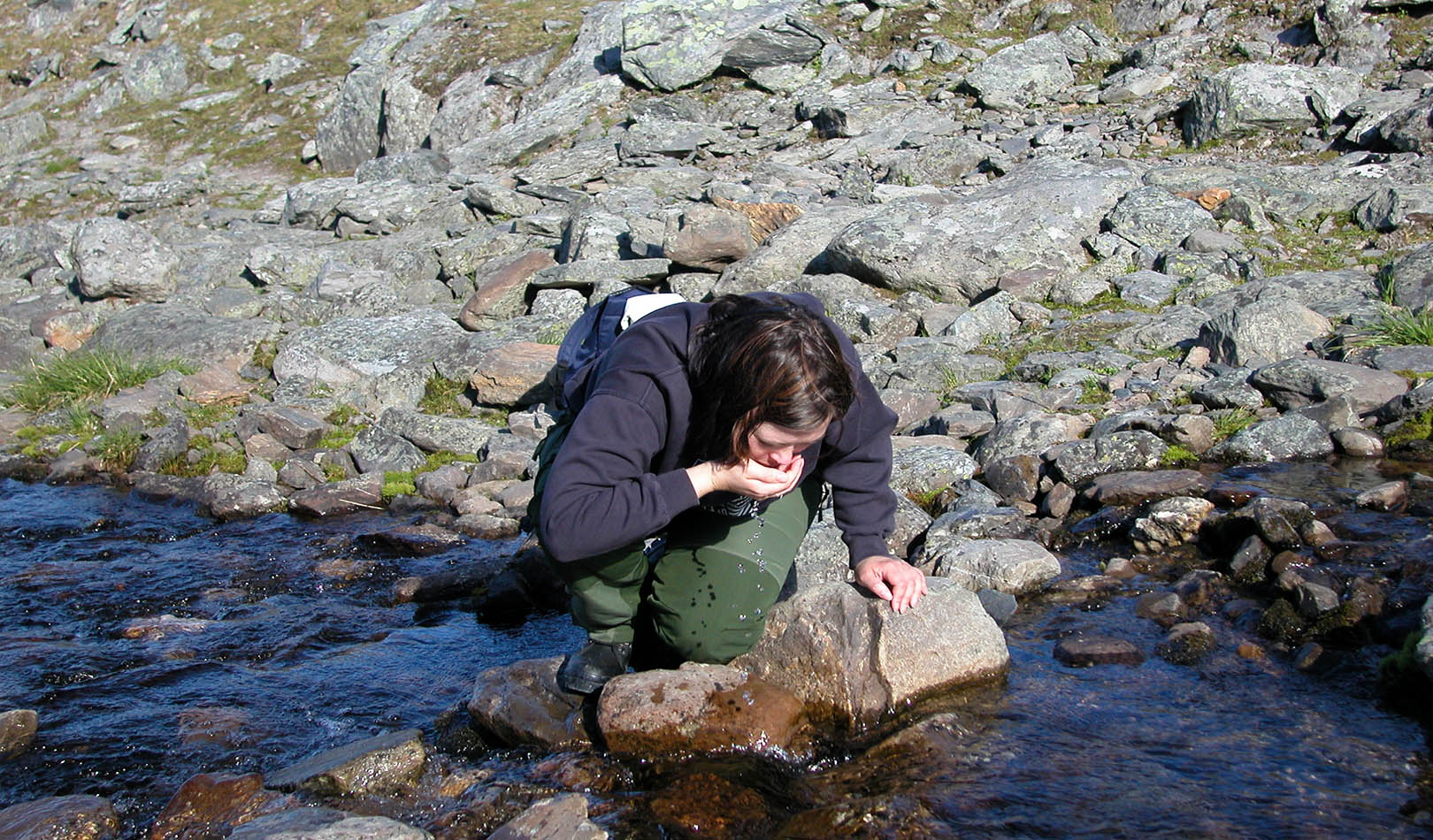 Hiker drinking from a mountain stream in Finnmark.