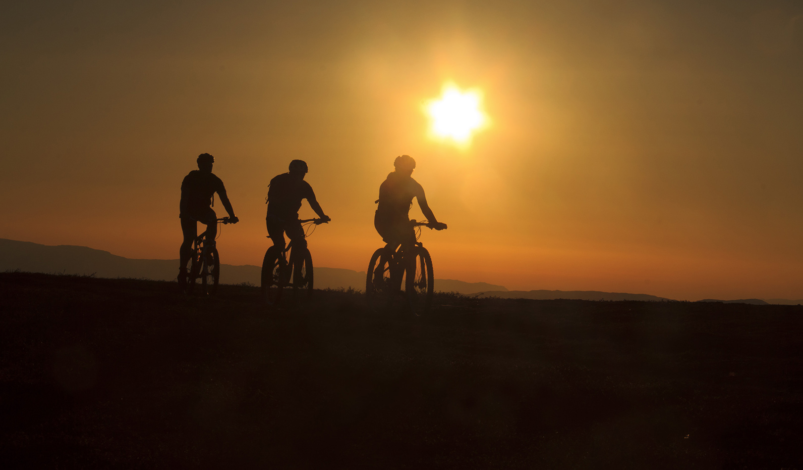 Silhouette of three cyclists on the Finnmark plateau in glowing midnight  sun.