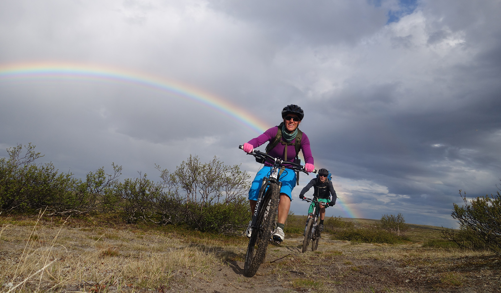 Two cyclists on the Finnmark plateu with rainbow and dramatic sky.