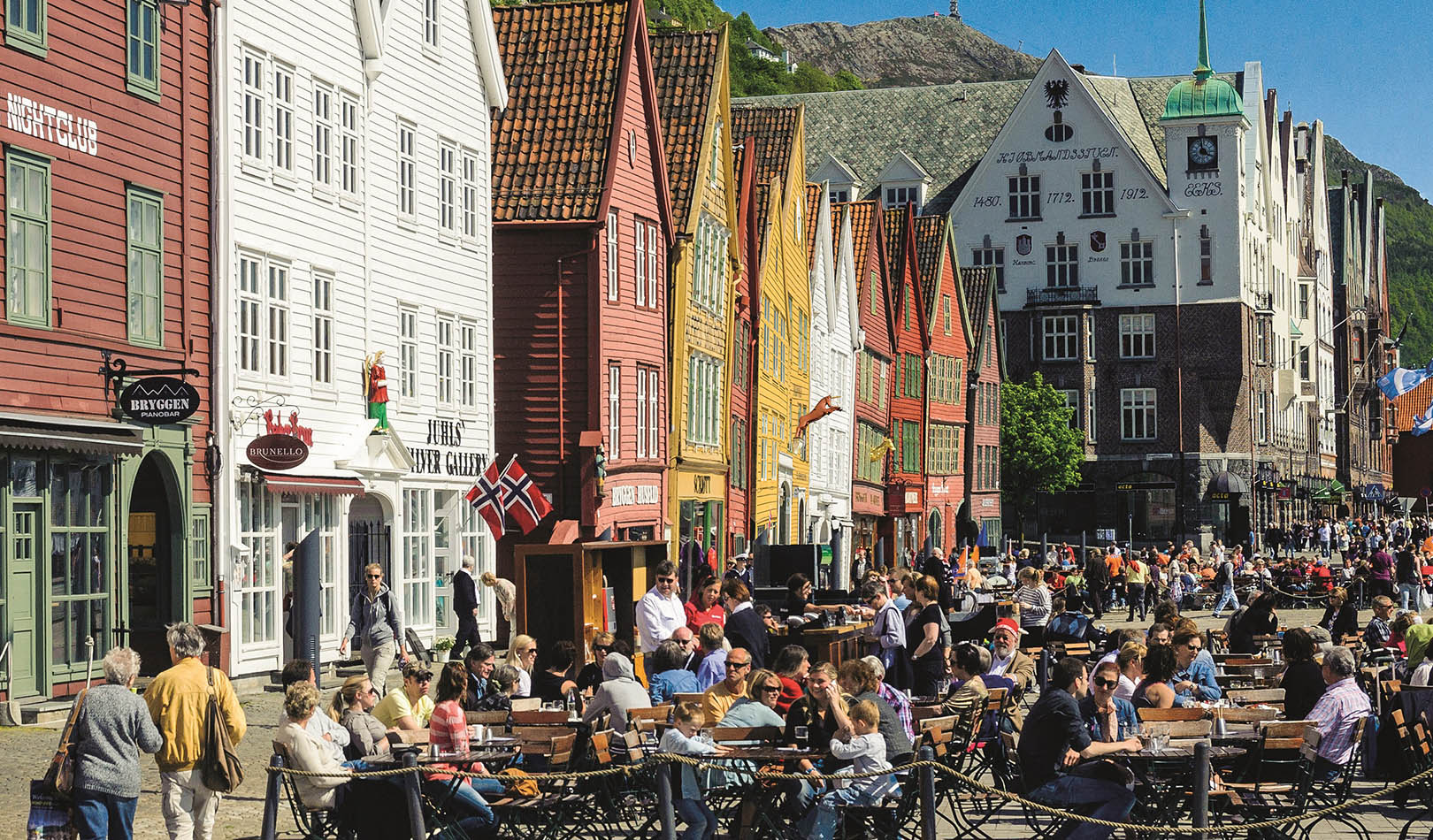 People eating and drinking at Bryggen in Bergen a sunny day.