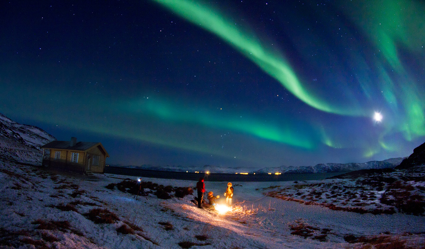 A family by a bonfire with the northern lights above them.