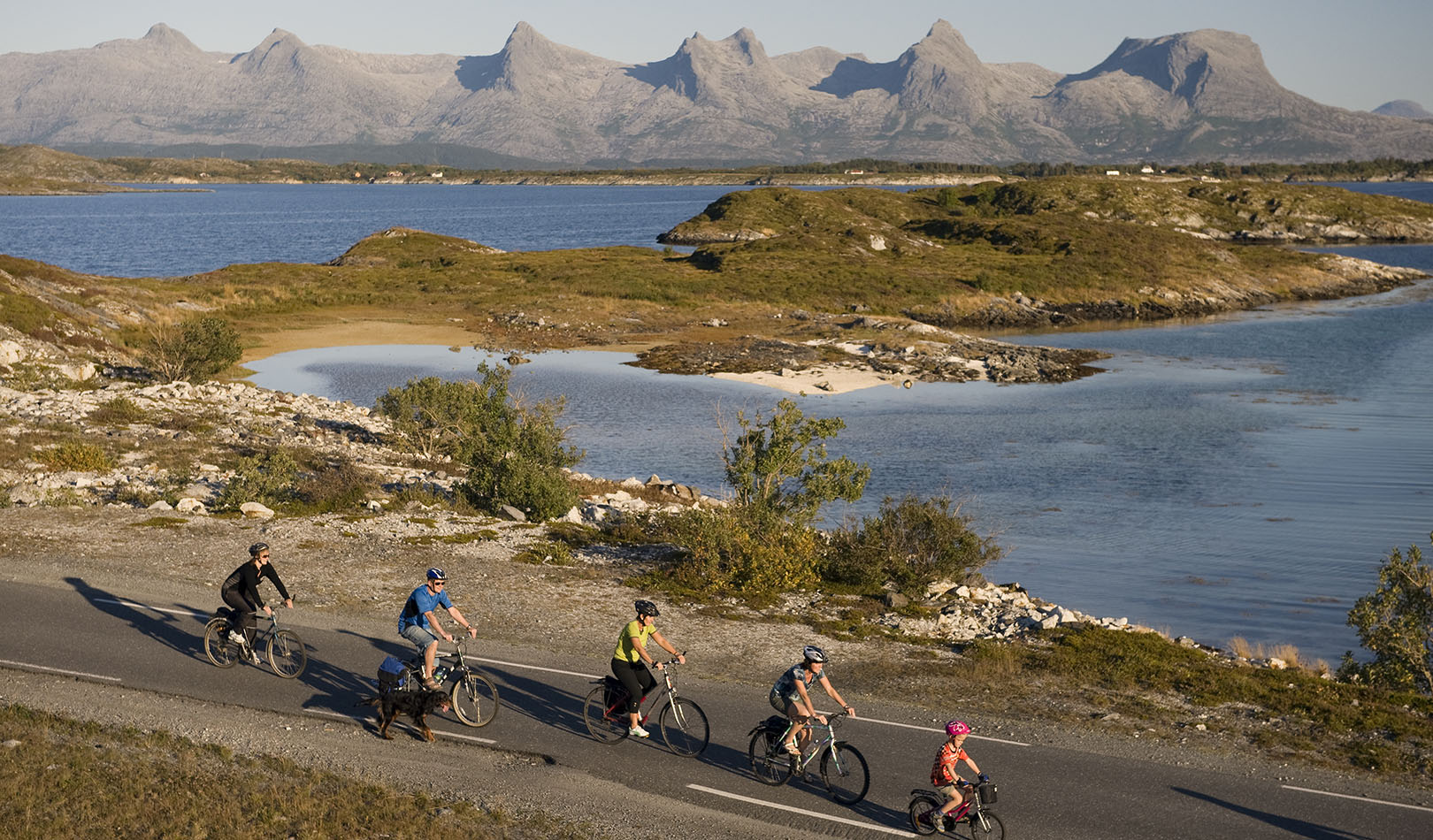 Cyclists with the mountainrange The seven sisters in the Background in Helgeland, Nordland.