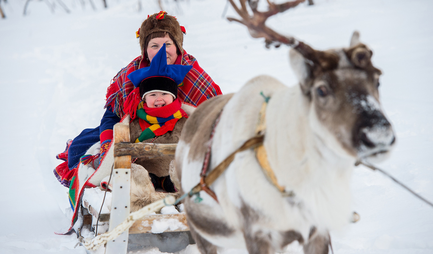 Sami woman and child on a reindeer sled.