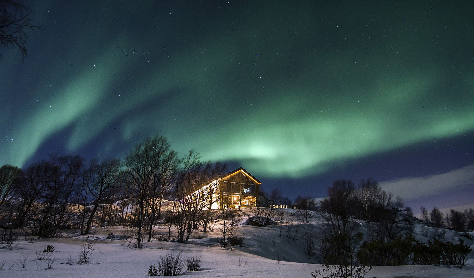 Northern light over a house with snowy landscape.