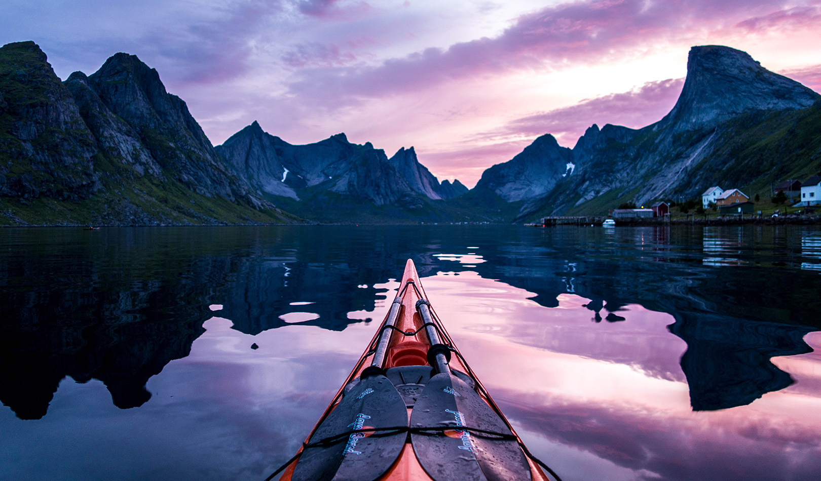 Kayak with spectacular view to mountains and purple sky on Kjerkfjord in Moskenes, Lofoten.
