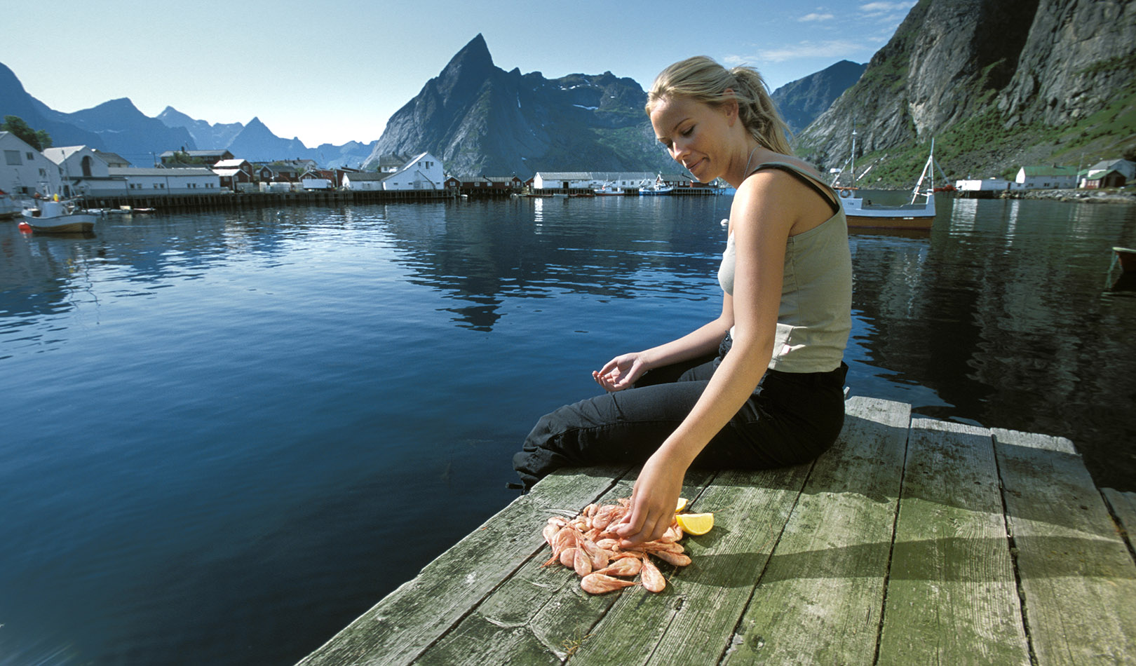 Woman eating shrimp in Lofoten, with houses, ocean and mountains in the background.