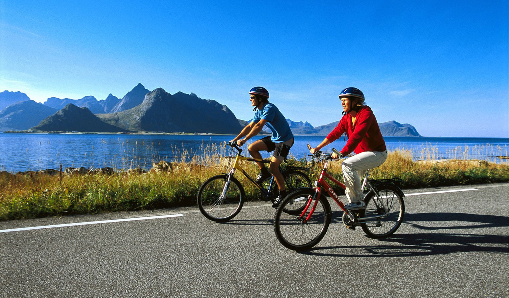 Couple cycling along a road in Lofoten with great vire to mountains and ocean.