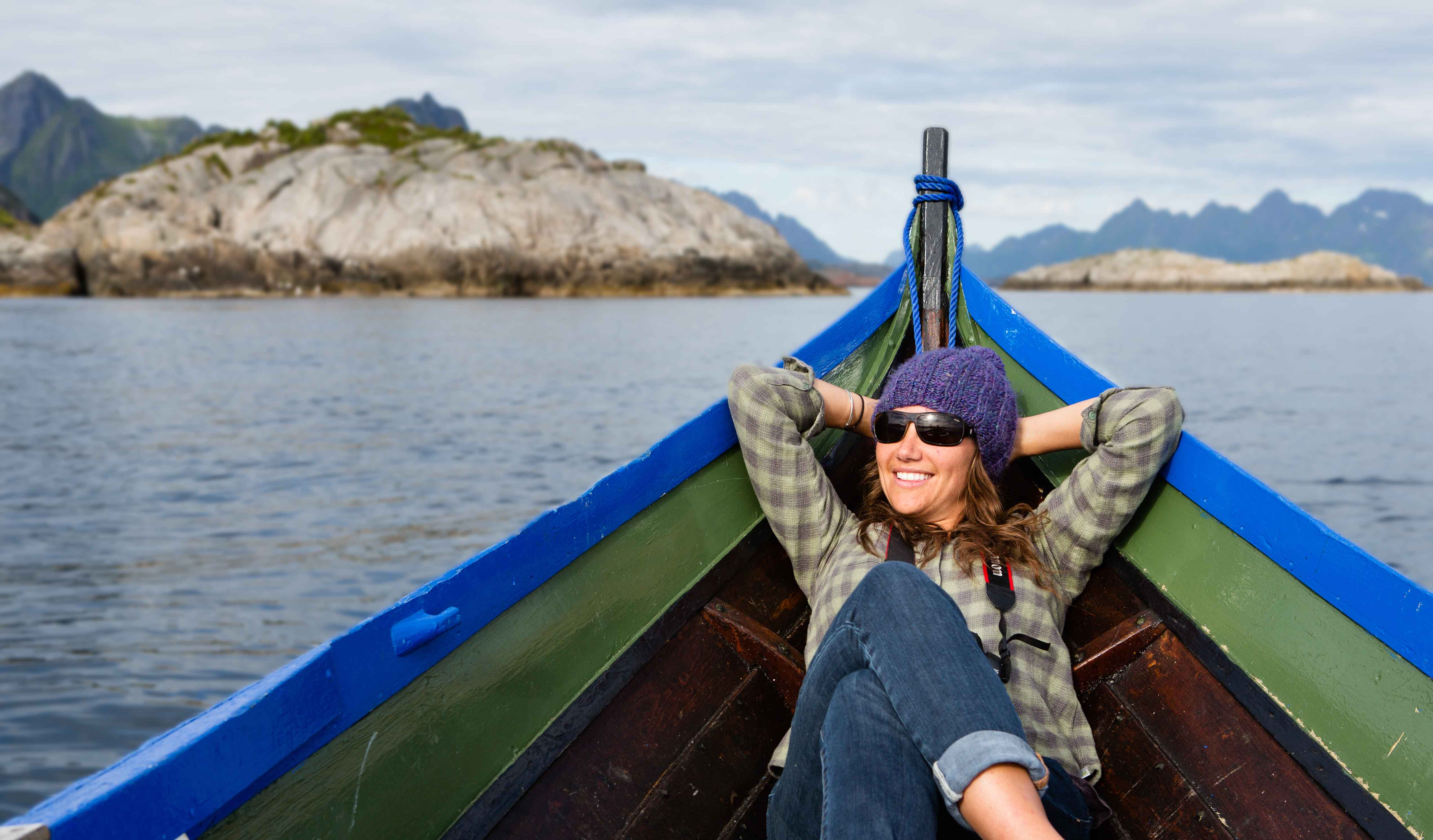 Woman relaxing in a wooden boat in Flakstad, Lofoten.