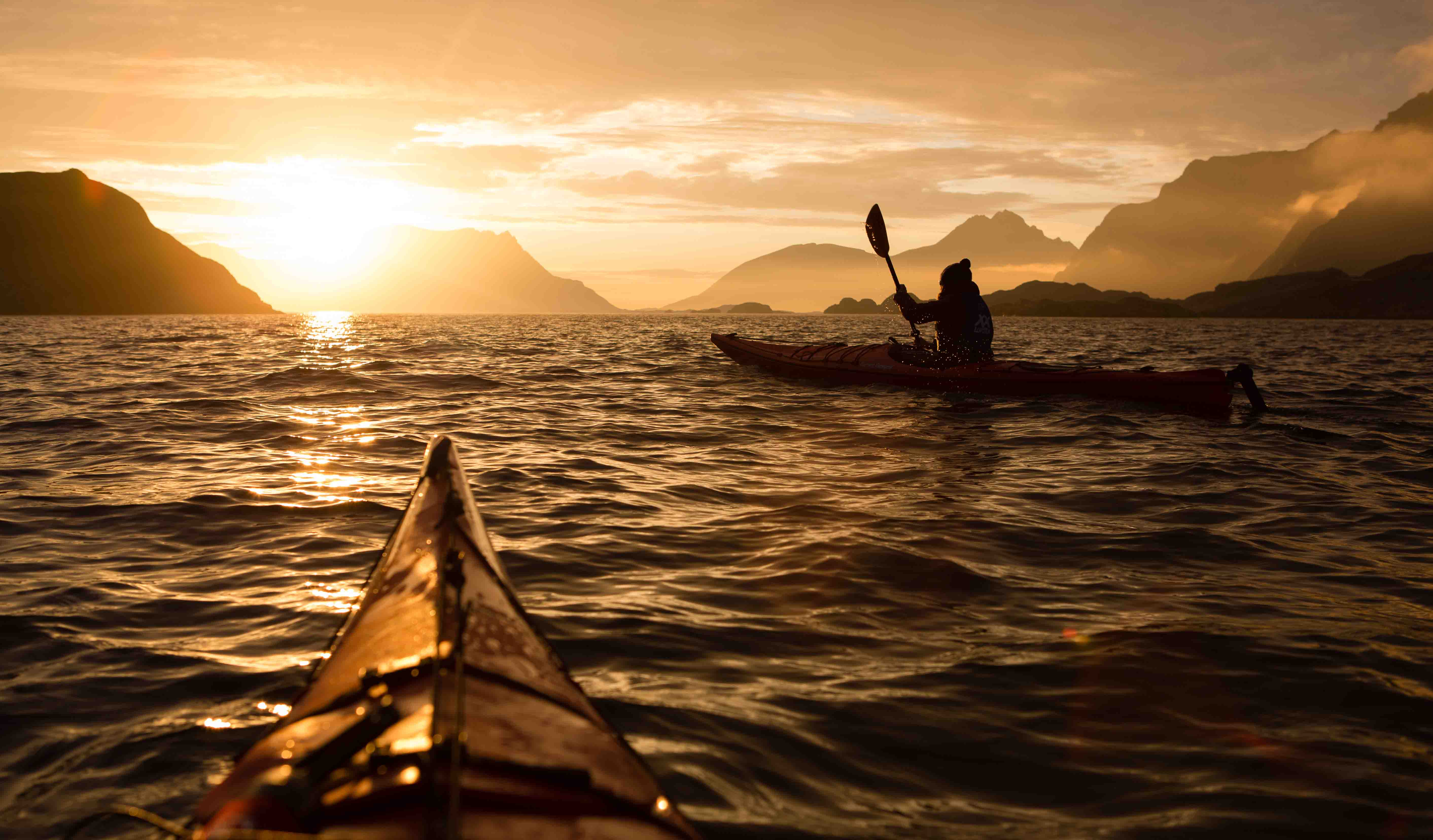 Two kayakers below the midnight sun on the coastline of Vestvågøy, Lofoten.