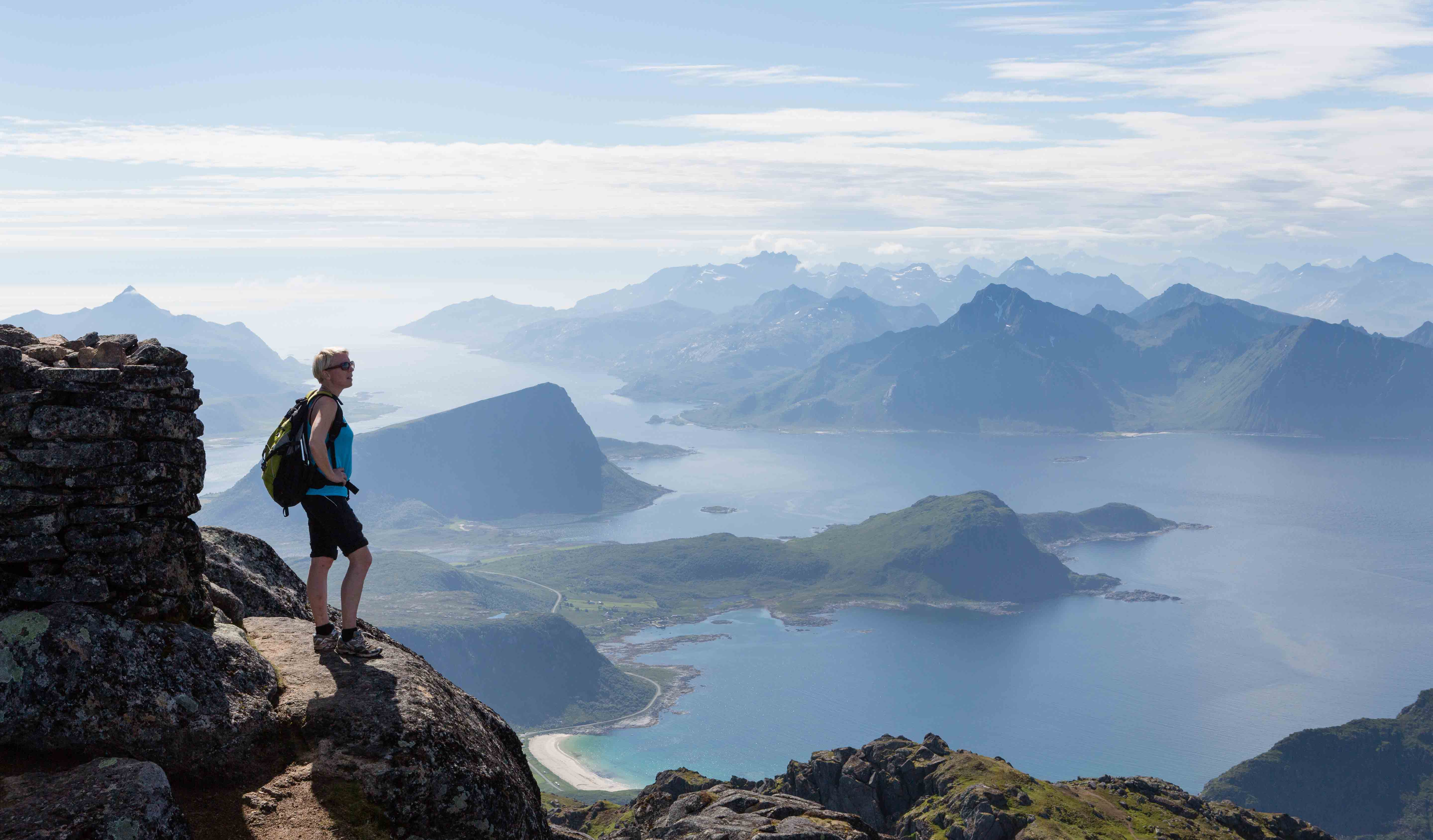 Woman enjoying the view from a mountain top in Flakstad, Lofoten.
