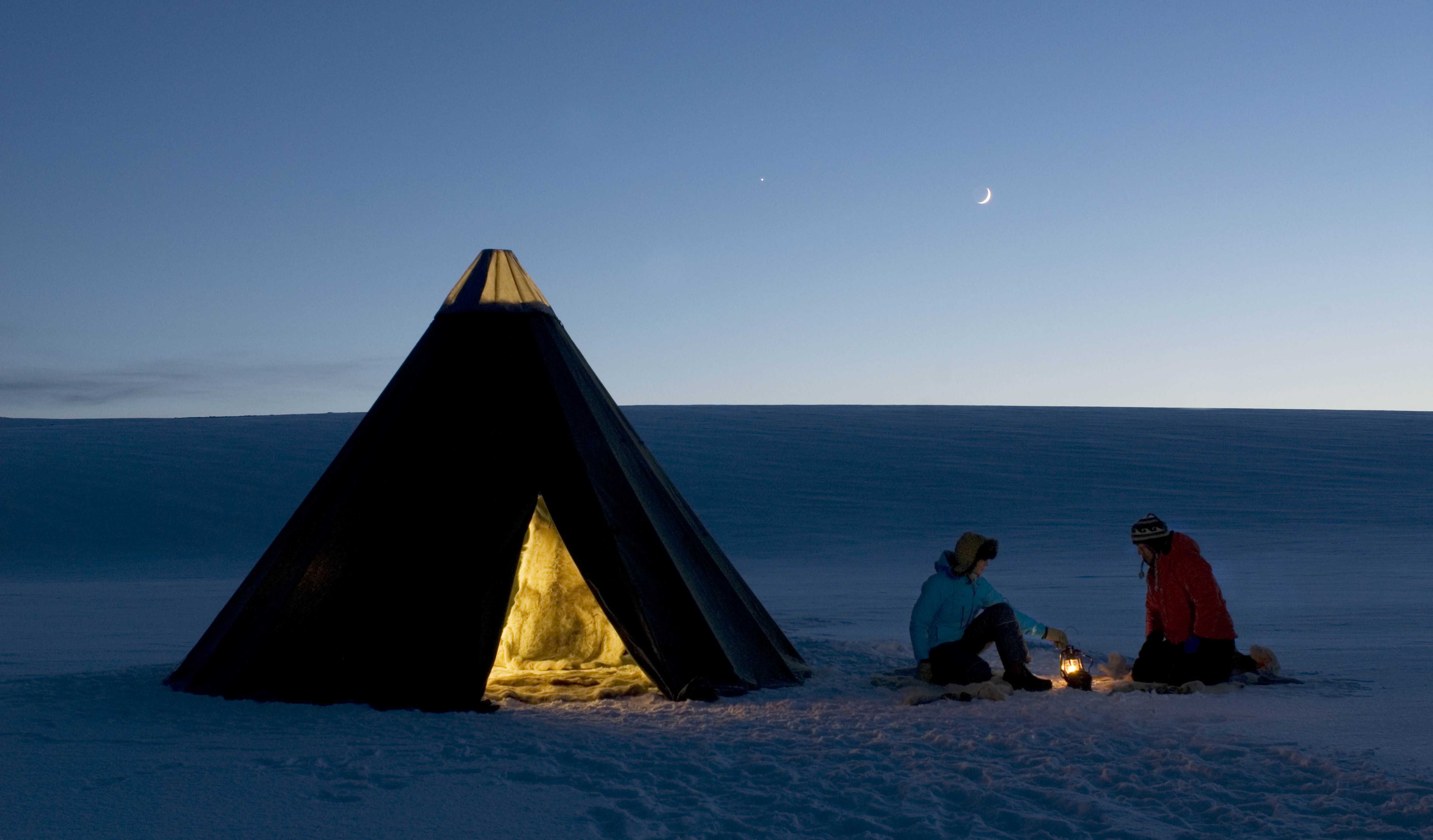 Sami lavvu and two people keeping warm on the mountain plateau of Finnmark.