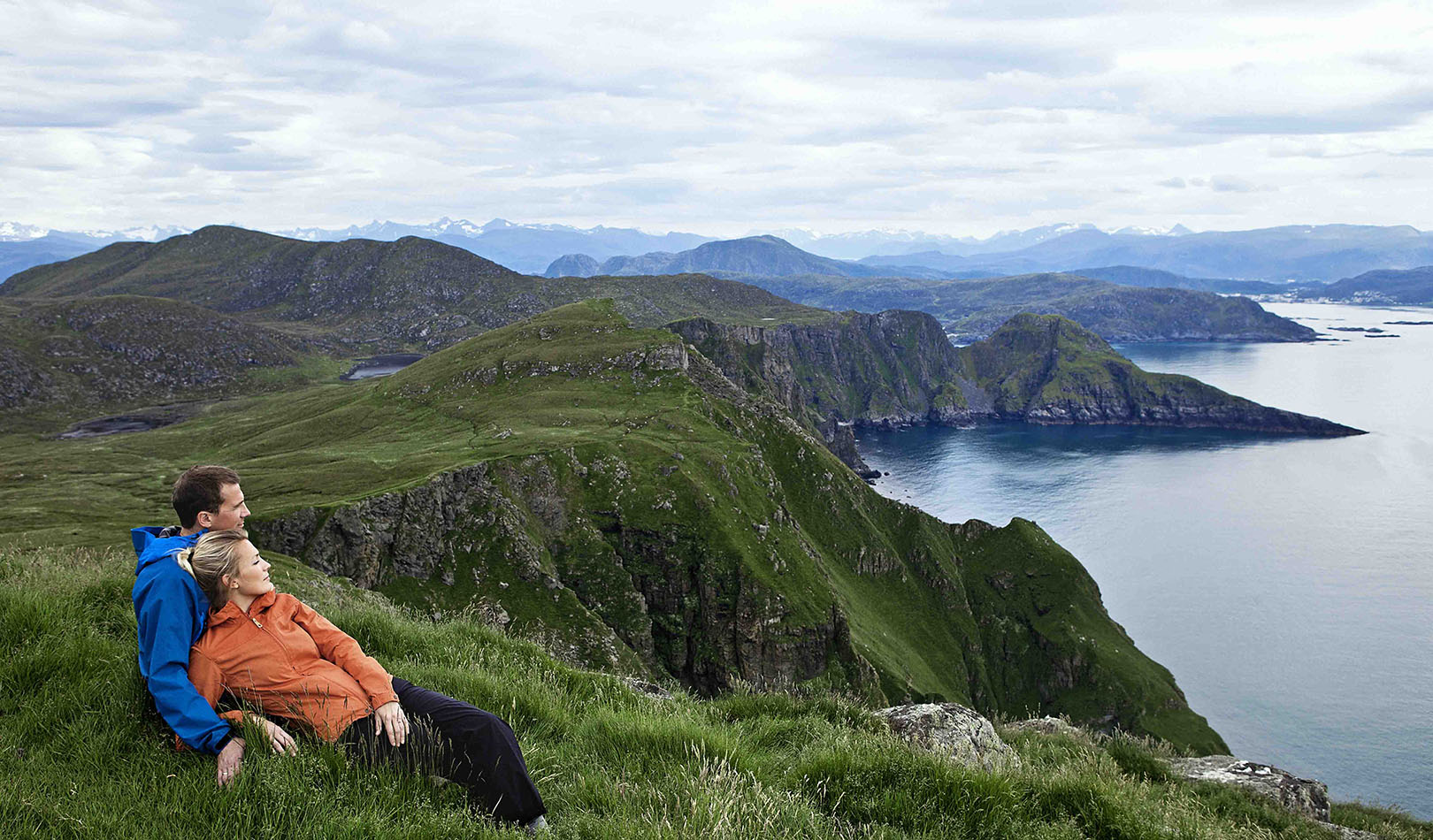Couple enjoying the view from a mountain on the Island of Runde, Sunnmøre.