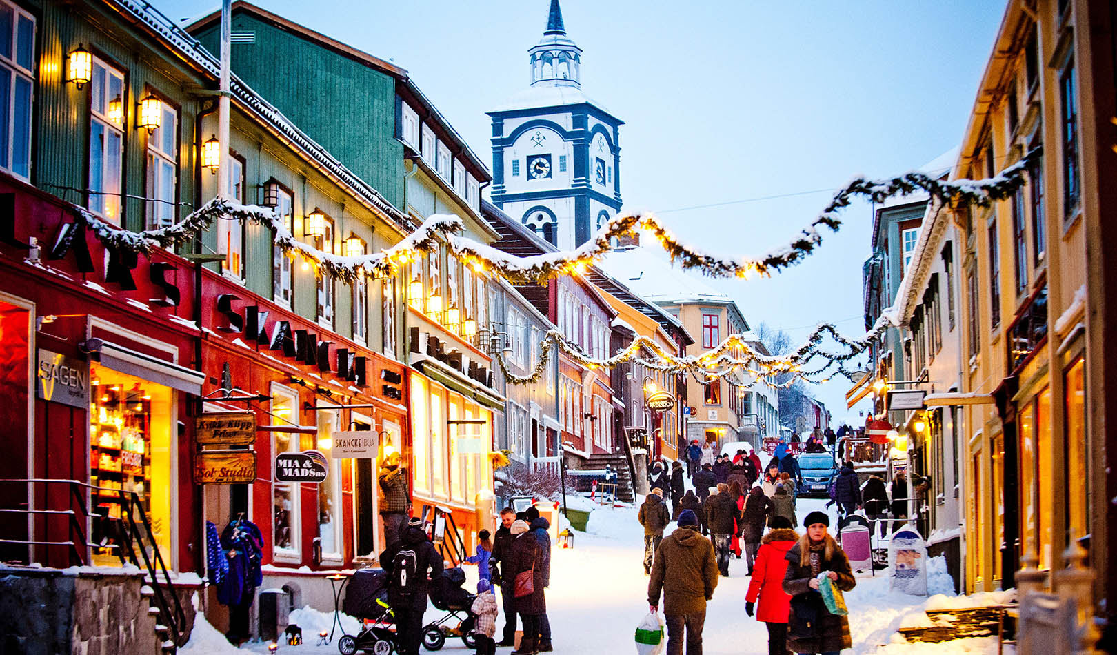 Christmas decorated street in Røros with busy shoppers.