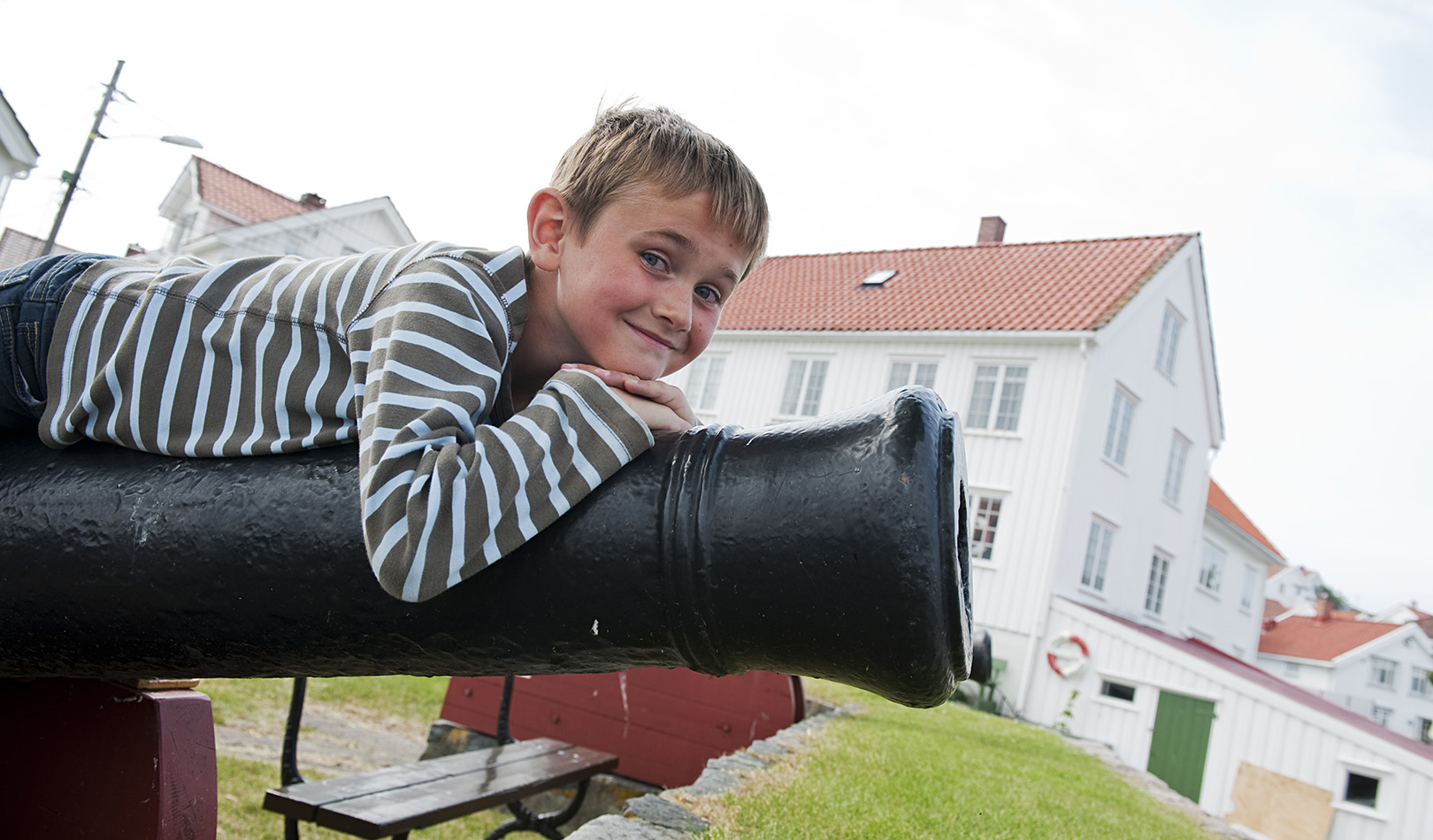 Boy lying on a canon with white buildings in the background, Risør, Sørlandet.