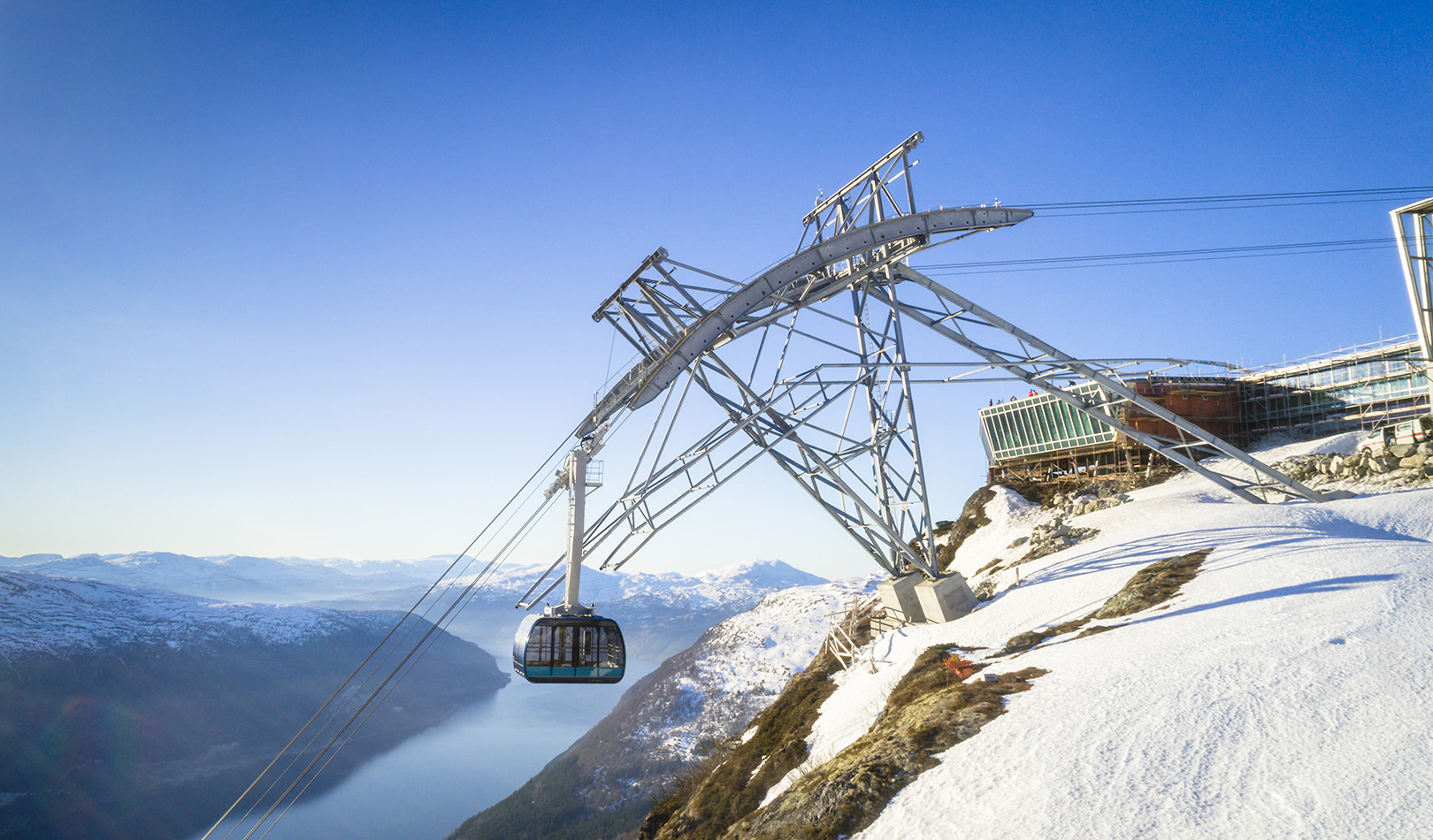 Loen Skylift on the mountaintop with view over mountains and fjords.