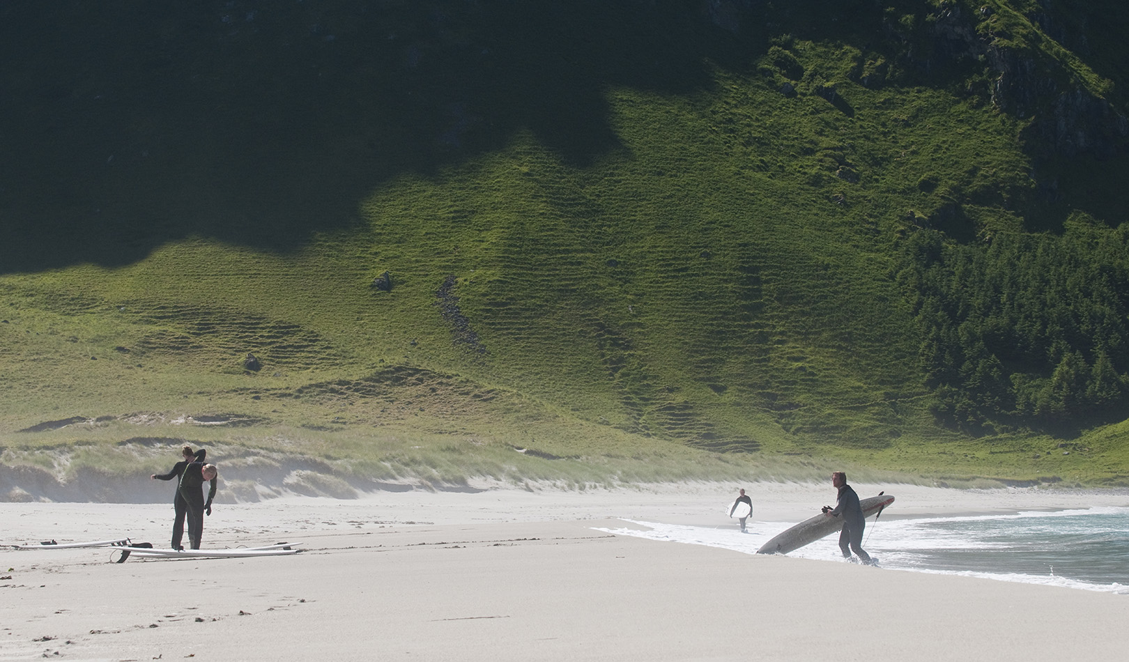 Surfers on Hoddevik beach with sand and a green mountainside.