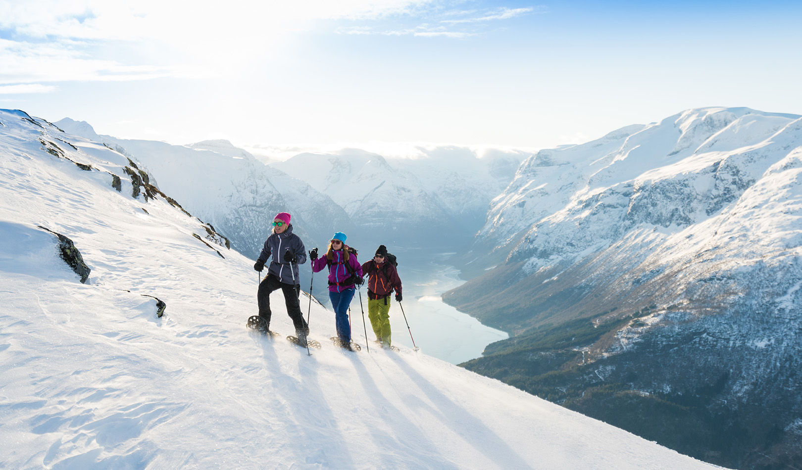 Three people walking with snowshoes on the mountain Hoven, Loen, Stryn with white, snowy mountains in the background.