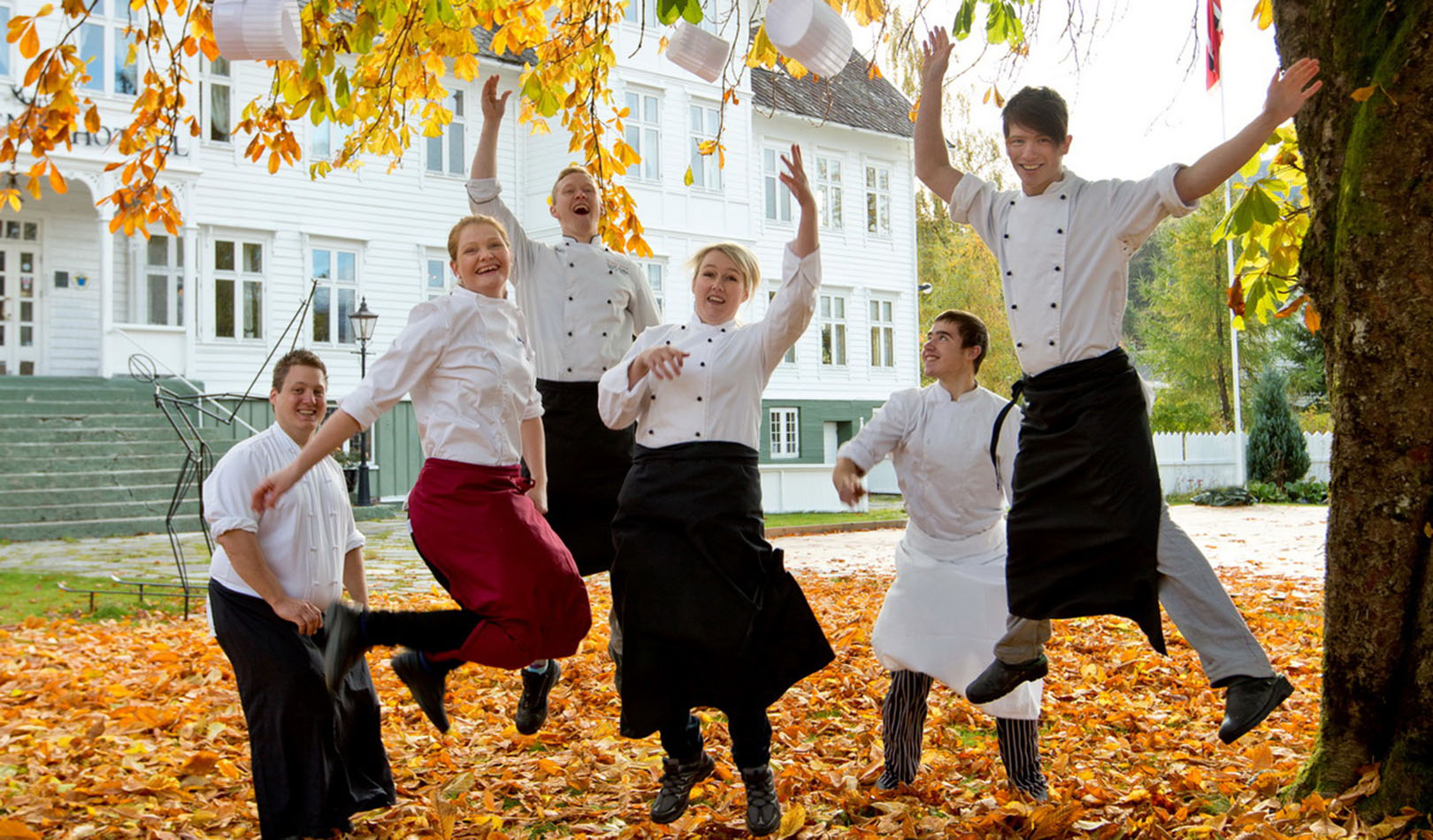 Jumping chefs outside Gloppen Hotel surrounded by autumn leaves.