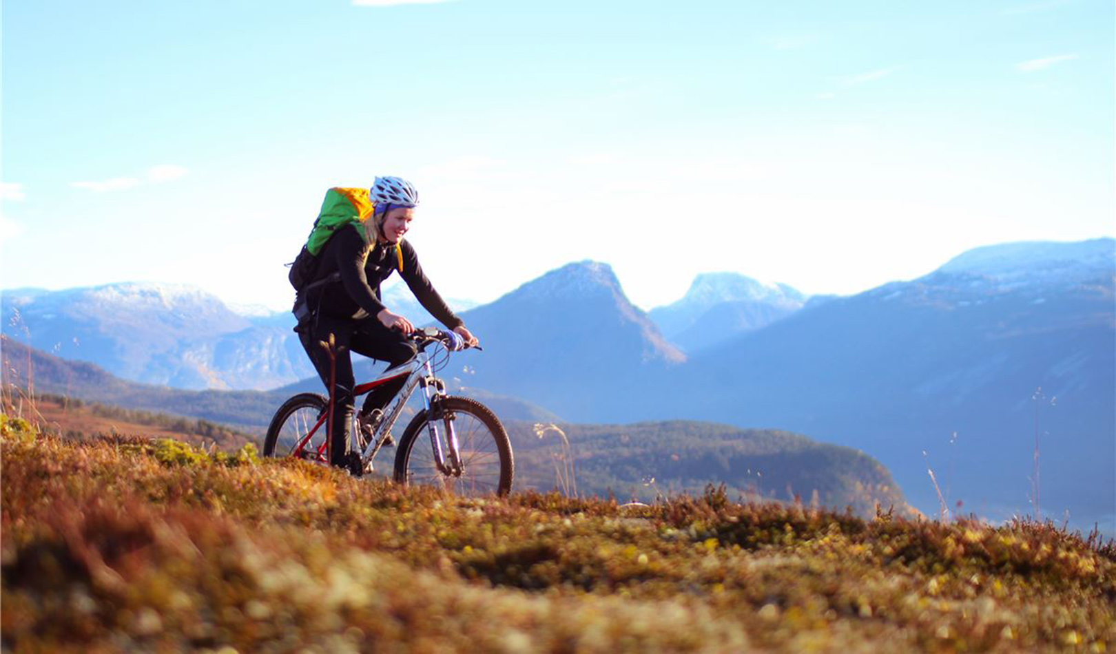 Woman cycling with mountains in the background.