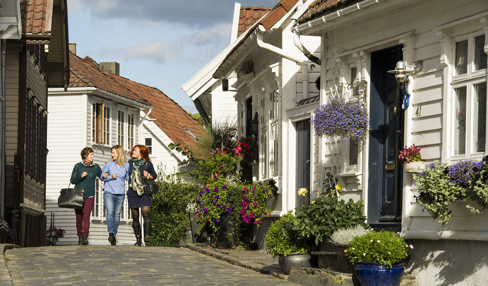 Three women walking amongst the white wooden houses in Stavanger.