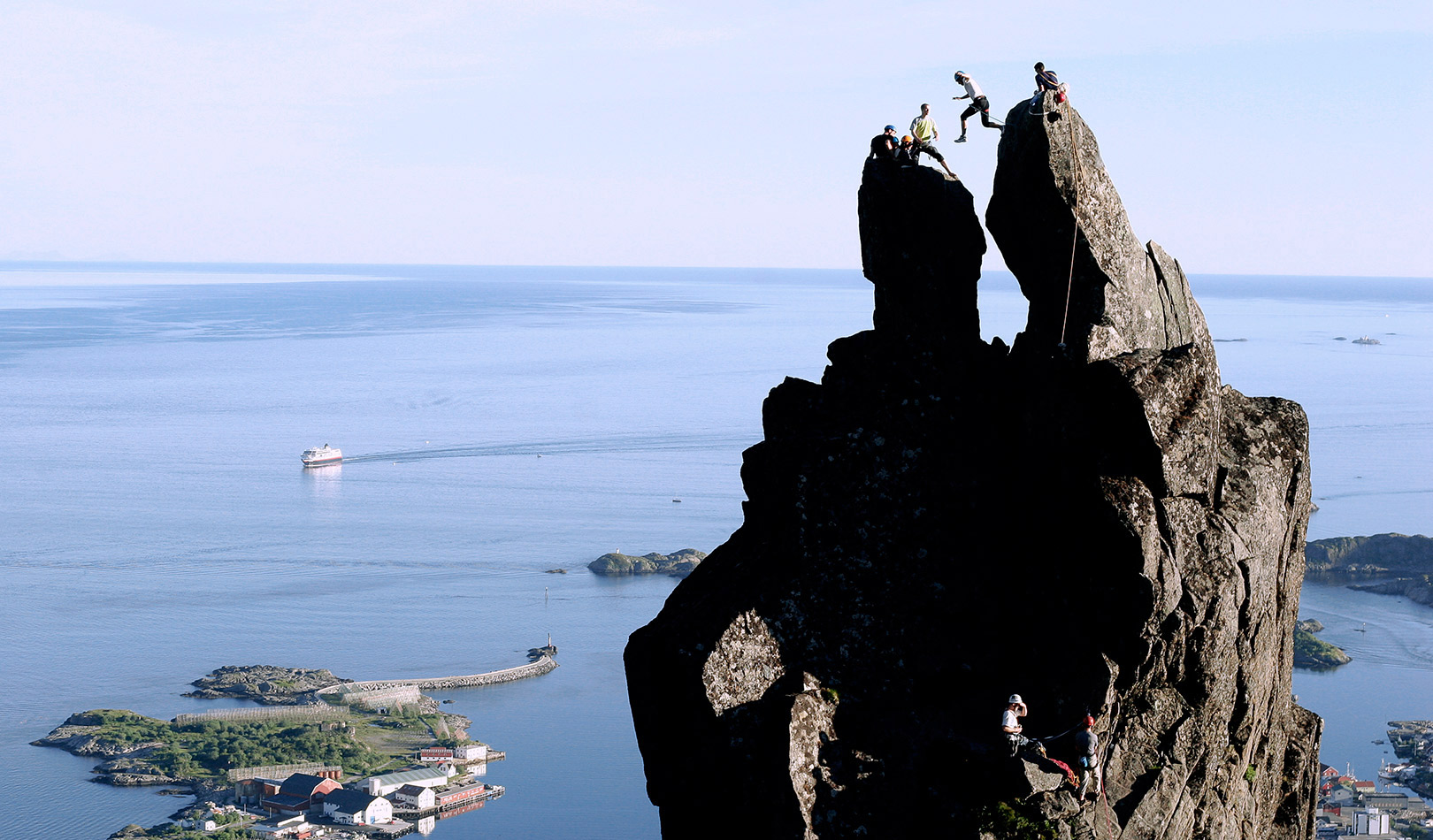 Man jumping from one cliff to the other on the top of the mountain Svolværgeita in the municipality of Vågan, Lofoten.