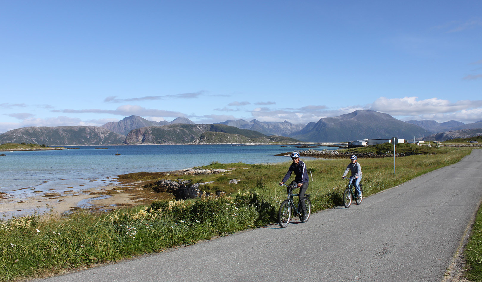 Two cyclists on a road outside Tromsø with ocean and mountains.