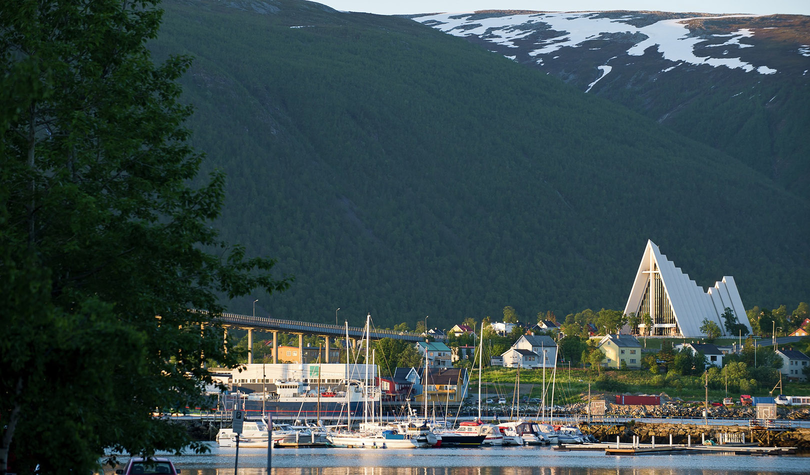 The iconic church of Tromsø with boats in the foreground and mountains in the background.