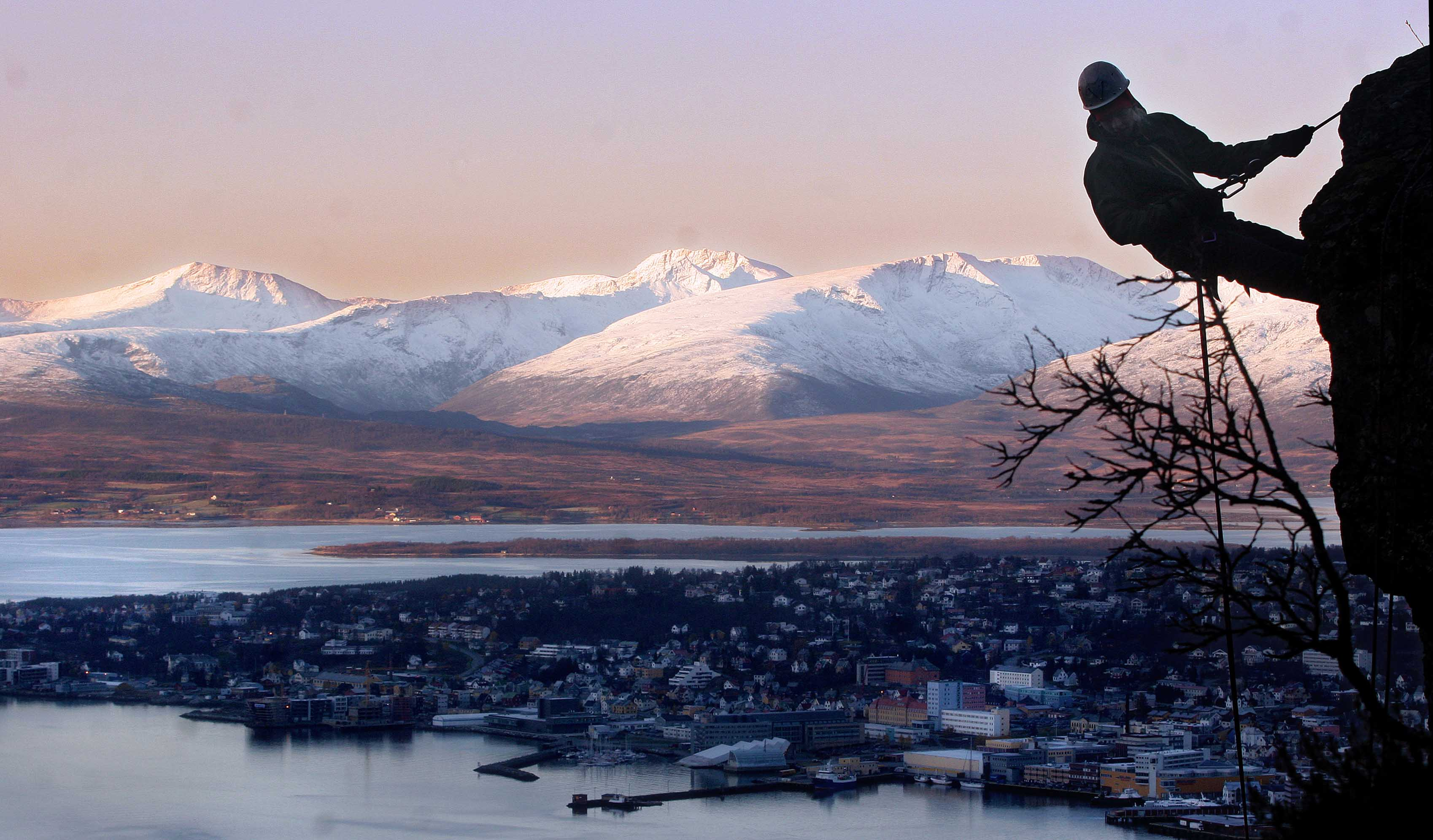 A rock climber in the foreground with the view of Tromsø.