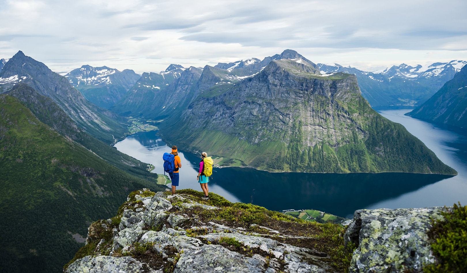 Two hikers enjoying the view on a mountain top in Sunnmøre,