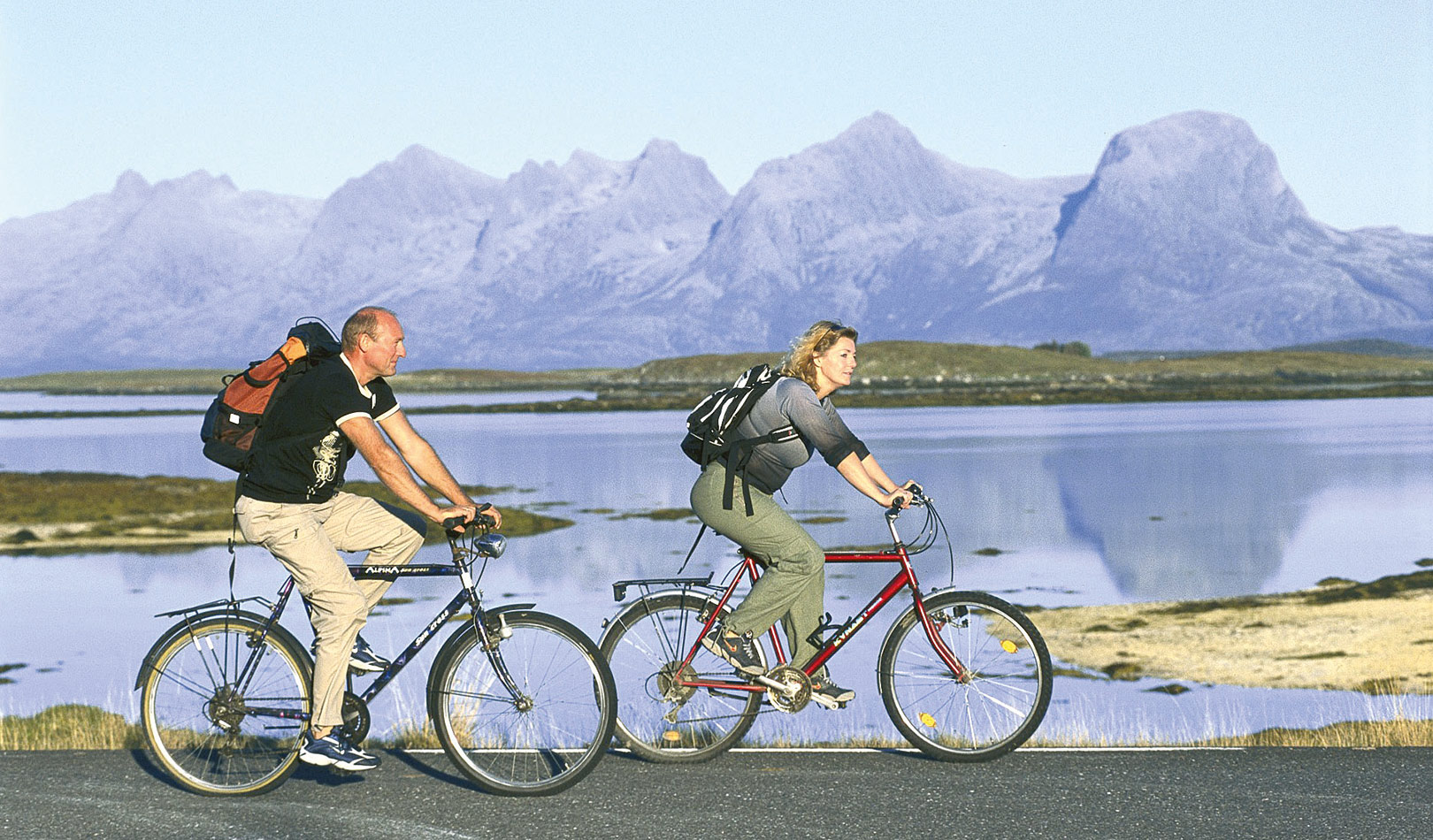 "Couple cycling with the mountain range ""the seven sisters"" close to Sandnessjøen."
